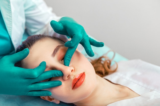 Rhinoplasty, the surgeon hands touches the patient s nose. plastic surgery and beauty concept - surgeon or cosmetologist hands touching female face. copy space.