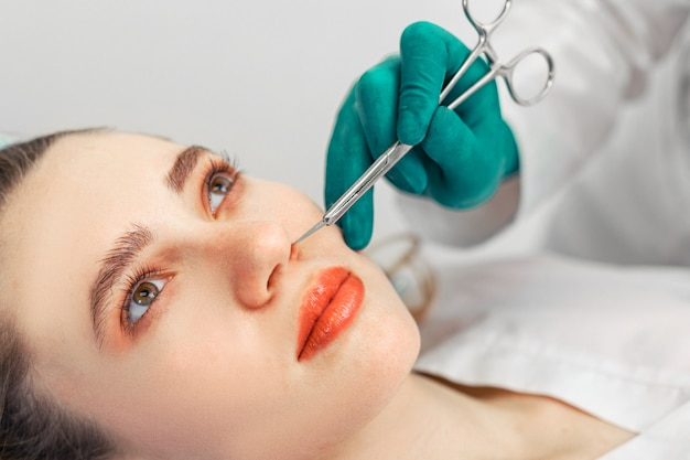 Ринопластика, хирург руками касается носа пациента.
