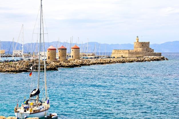Rhodes landmark - mandraki port, the medieval lighthouse, windmills