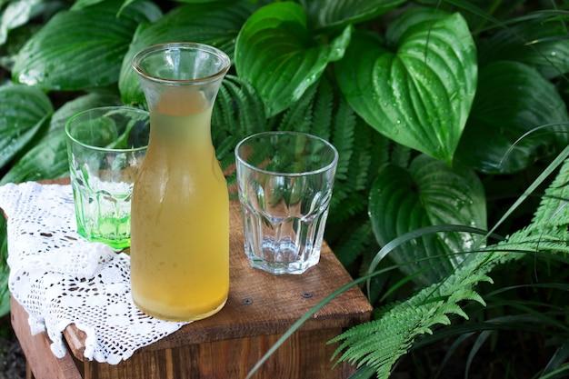透明な水差しのルバーブコンポートと庭の木製の椅子にグラス。