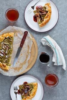 明るい灰色の背景にナイフ、フォーク、グラスを置いた皿にルバーブのパイ