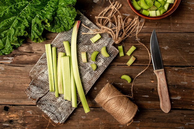 Rhubarb stalks. stems and leaves of fresh rhubarb on an old wooden table. cooking rhubarb. banner format. space for text. top view