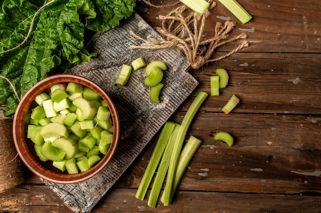 Rhubarb on wooden table. fresh rhubarb in bowl. stems and leaves of fresh rhubarb. long banner format. copy space for text