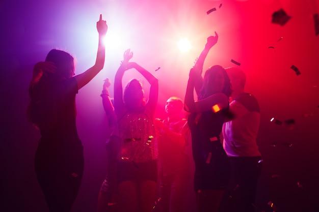 リズム。シルエットの人々の群衆は、ネオンの光の背景のダンスフロアに手を上げます。ナイトライフ、クラブ、音楽、ダンス、モーション、若者。パープルピンクの色と感動的な女の子と男の子。