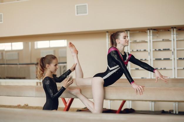 新体操。女の子の体操選手は、さまざまな体操やジャンプを行います。子供とスポーツ、健康的なライフスタイル。