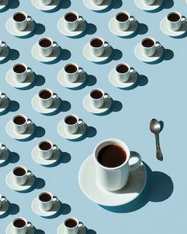 Ритмичный узор из чашек с кофе на синем фоне. контрастные тени, выборочный фокус.