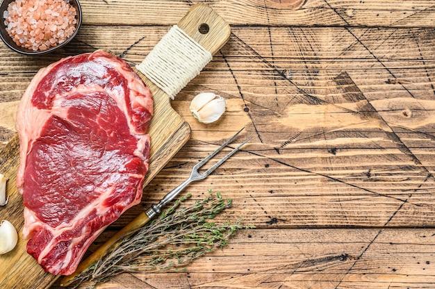 リブアイまたはカウボーイステーキ。生霜降り牛黒アンガス、リブアイ。木製の背景。上面図。スペースをコピーします。