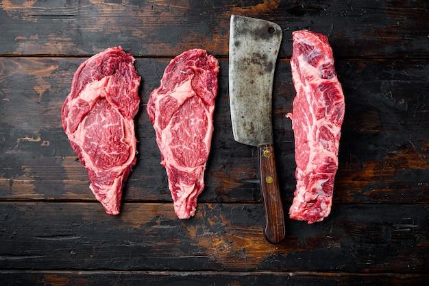 립아이 스테이크 신선한 생 쇠고기 차돌박이 프라임 고기 ribeye 세트, 오래 된 어두운 나무 테이블 테이블, 평면도 평면 누워