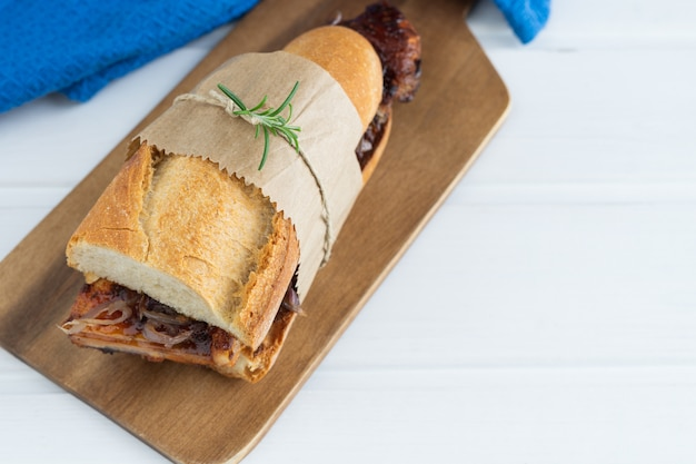 Rib sandwich in barbecue sauce on a white wooden base