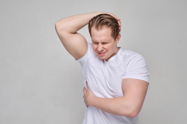 白いシャツを着た男性がrib骨の領域をマッサージします。痛みと神経学の概念。