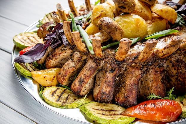 白い木製のテーブルにおいしい肉、サラダ、rib骨、野菜のグリル、ポテトの肉プレート