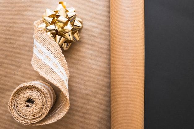 Лента лук и ткачество ленты на свернутую коричневую бумагу на черном фоне