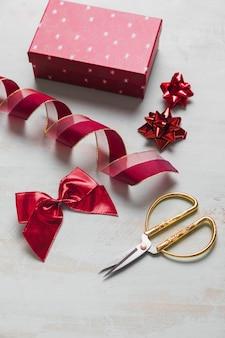 Nastro e fiocchi vicino a forbici e regalo