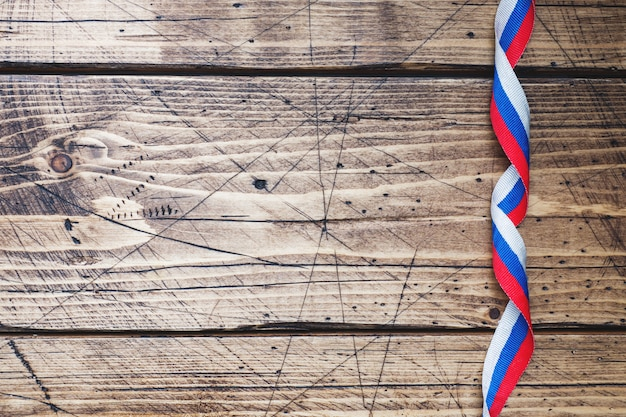Ribbon in colors of russian flag tricolor on wooden background copy space