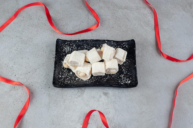 Ribbon laid around a black platter of marshmallows on marble surface