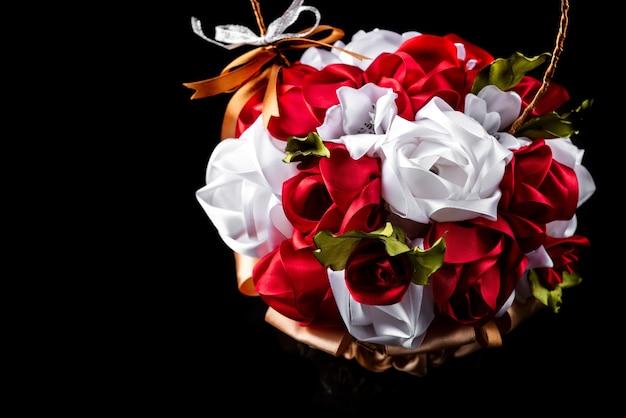 黒い表面にリボンのバラの花。