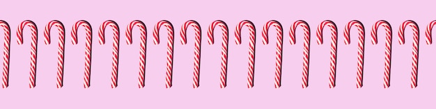 Лента бесшовный фон красные и белые рождественские конфеты посохи