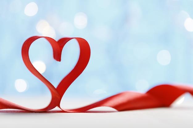 ライトと青い背景の上のハートの形をしたリボン。バレンタインデーのコンセプト