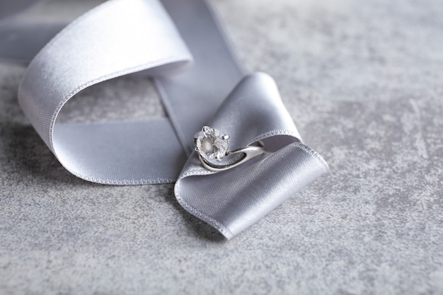 Ribbon with beautiful engagement ring on table