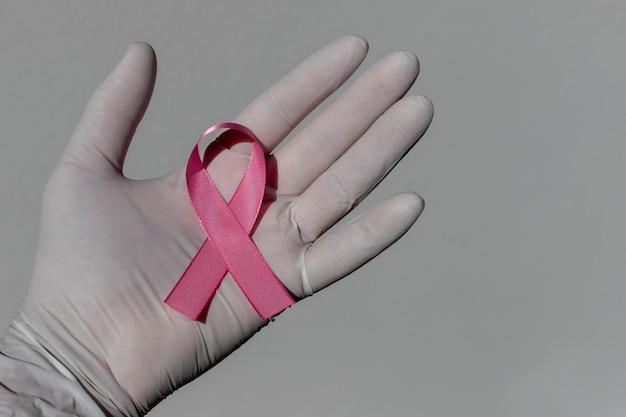 수술용 장갑으로 손에 분홍색 활이 달린 리본. 유방암 예방 캠페인. 분홍빛 10월.
