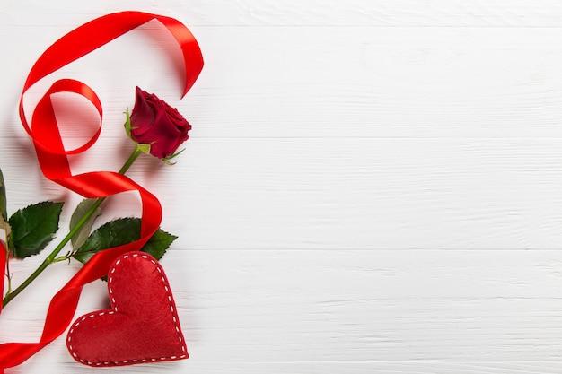 白いテーブルに赤いバラ、ribbonndハート。