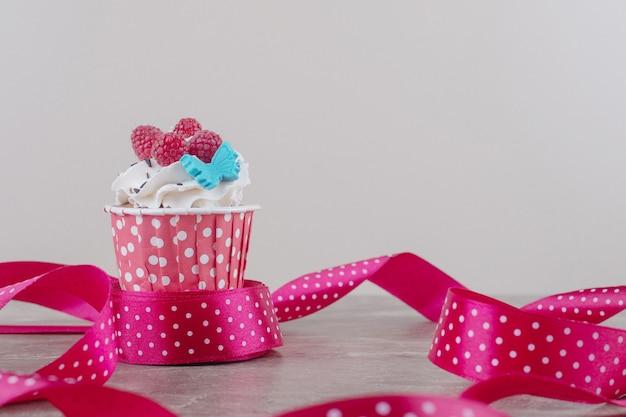 대리석에 크림을 얹은 컵 케이크 주위의 리본