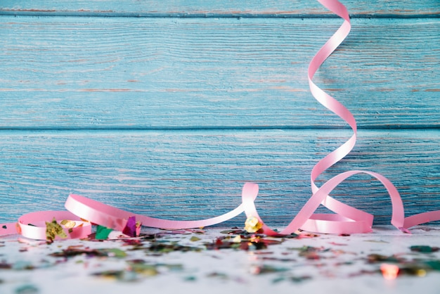 Ribbons and confetti on blue wood