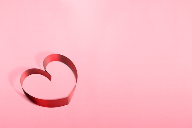 Ribbons shaped as hearts over pink background