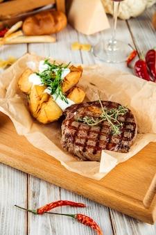 Стейк из говядины рибай с печеным картофелем и сметаной