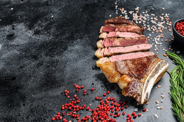 Ribeye steak on the bone with salt and pepper. grilled beef meat.  black background. top view. copy space.