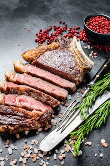 Ribeye steak on the bone with salt and pepper. grilled beef meat.