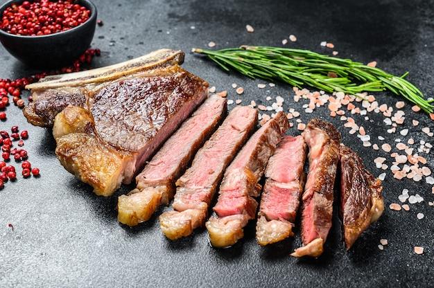 Ribeye steak on the bone with salt and pepper.
