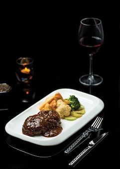 Ribeye steak in teriyaki sauce with glass of burgundy