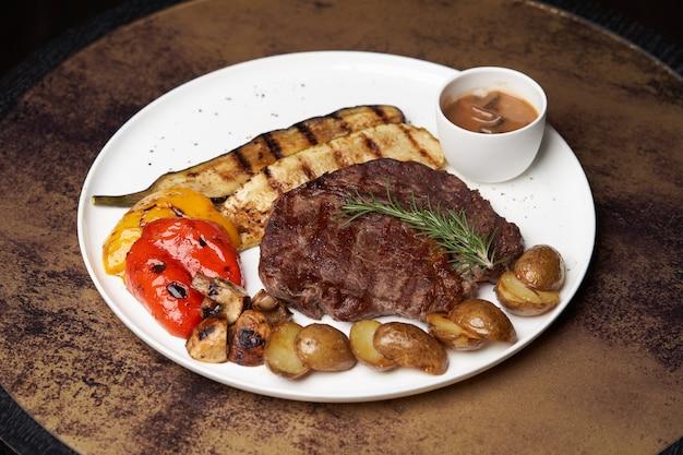 튀긴 감자와 ribeye 스테이크. 흰색 접시에 쇠고기 스테이크와 구운 된 야채입니다. 고급 레스토랑 음식 테이블
