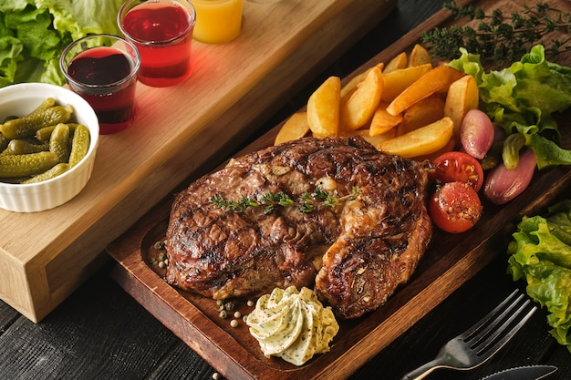 Ribeye steak with potatoes, onions and baked cherry tomatoes