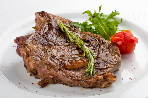 Ribeye steak with rosemary on a white plate