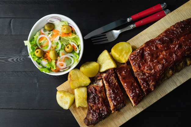 Ribs in barbecue sauce and potatoes on a wooden board