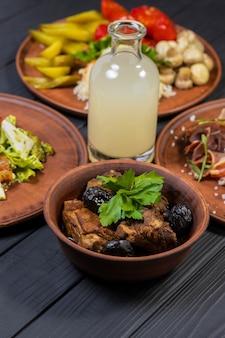 Ребрышки с черносливом в тарелке с вином на черном деревянном фоне