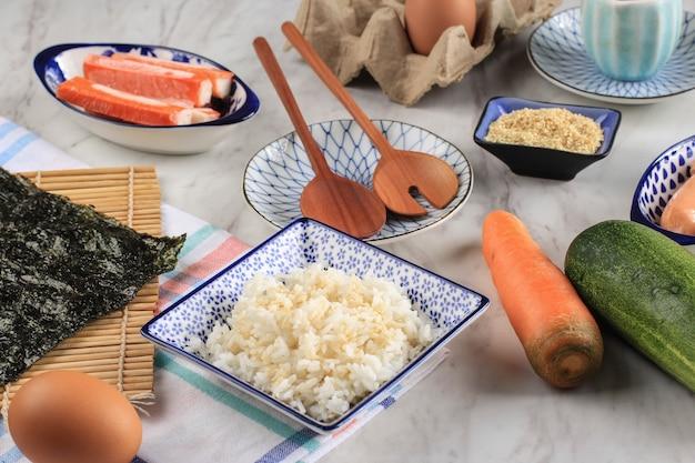米と別のキンバプ/キムパプの材料/韓国のライスロールを白い大理石のテーブルに載せます。海苔・海苔、にんじん、塩、ごま、きゅうり、蟹カマ、ソーセージ。