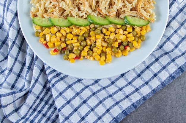 Салат из риса и кукурузы в тарелке на кухонном полотенце, на мраморной поверхности.