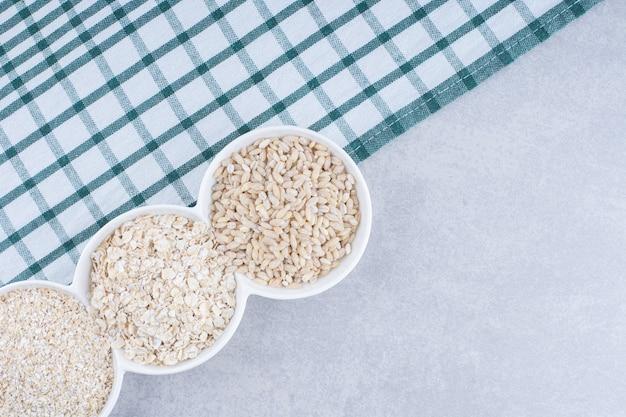 На блюде на мраморной поверхности порциями сложены рис и овес
