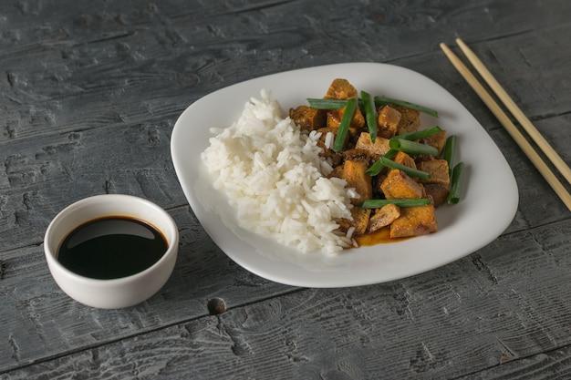 Рис и жареный тофу в белой миске на столе. вегетарианское азиатское блюдо.