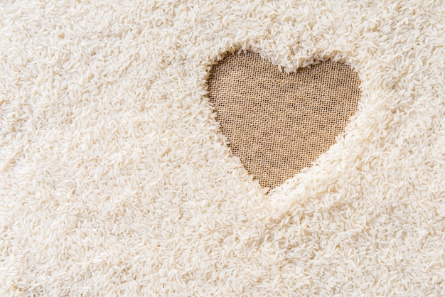Rice background space in the corner of a heart. sackcloth is background