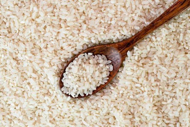 Фон риса с крупным планом деревянной ложкой. вид сверху.