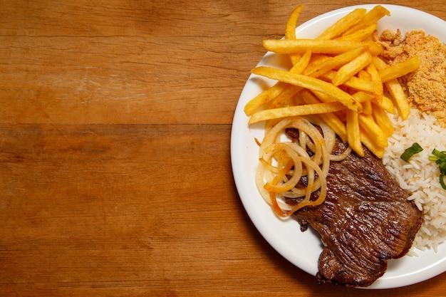 Рис, фасоль, картофель фри и стейк из говядины