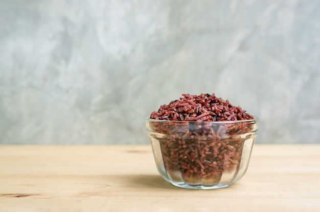 Rice berry in a bowl on a wooden table.