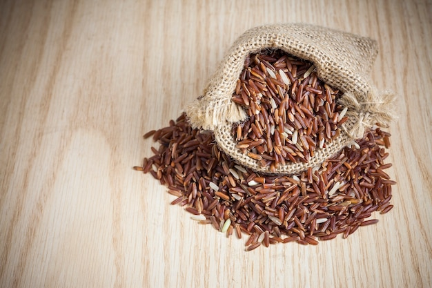 Rice berry in a sack on a wooden background.