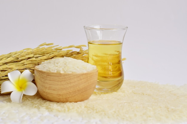 Rice bran oil in a glass with uncooked jasmine rice in wooden bowl & ear of rice on white