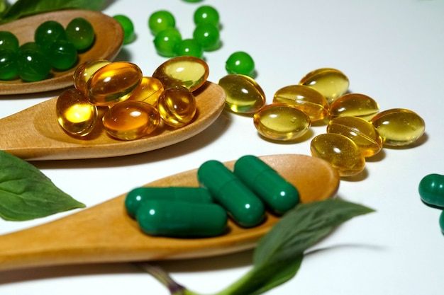Rice bran oil and herbal vitamins in a capsule on a wooden spoon with white background