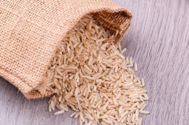 Коричневый рис просыпается из мешка на столе.